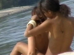 Cute lesbian teens enjoying sunbathing at nudist beach