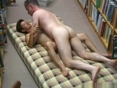 Mature couple fucks on a matress in a library