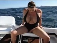 Busty chick rides toy on boat