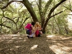 Blonde teen rubs her girlfriend's cunt in the forest