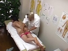 A plump Asian is showing her boobs and hairy pussy in the massage room