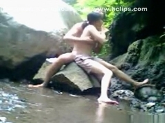 Asian girl fucks her bf on a rock in the river