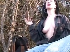 smokBrunette babe giving blowjob while smoking in the park