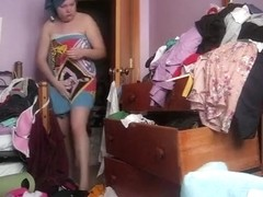 Chubby woman changes in a messy room