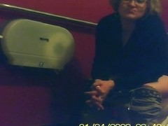 Mature unsuspecting female sitting on a toilet