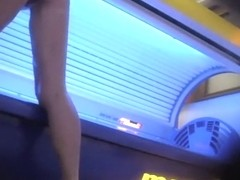 Mature lady wipes the tanning machine