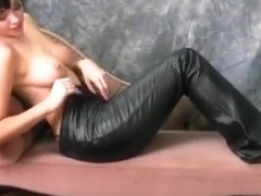 Naked babe loves the feel of tight leather pants around her big  ass